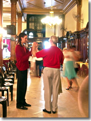 Gustavo, the postcard Argentine tango teacher, taking a coupel of tourists in hand to teach them the tango.