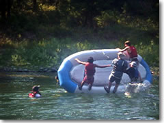 The boys learn river rescue techniques by purposefully flipping their raft, then learning to right it again in the rapids